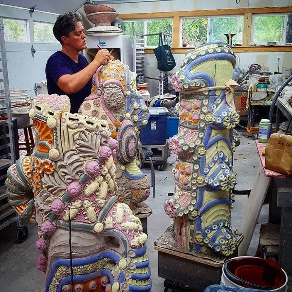 Diana Kersey, working in her home studio, brushes paint onto the dry, unfired sculptures destined for VIA Five Points. - COURTESY