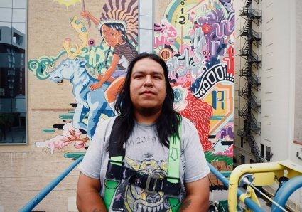 """Rudy Herrera stands in front of """"The Last Parade"""" recently. - COURTESY PHOTO / RUDY HERRERA"""