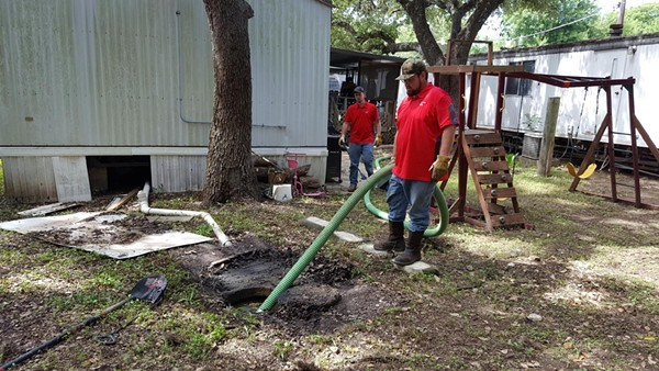 Maintenance staff clean up raw sewage outside an Oak Hollow home in October 2016. - CITY OF SAN ANTONIO / RAY GURZA