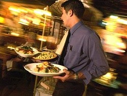 Waiter Remmy Castillo rushes out an order on a busy Thursday evening at Dolores del Rio.