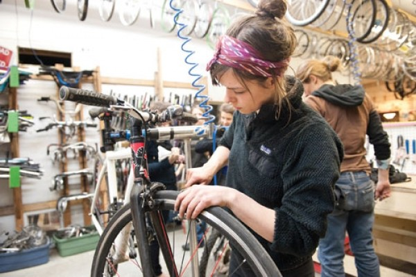 Bike Collective volunteer Tara Christensen tinkers during Women's Night - NIKI CHAN