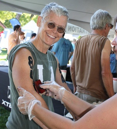 LYN CHRISTIAN OF SALT LAKE CITY GETS HER NUMBER STAMPED ON HER ARM THE DAY BEFORE THE TRIATHLON. - BY WINA STURGEON