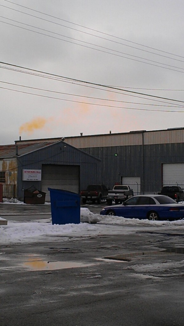 Neighbors of Accurate Recycling in Murray say the plume of smoke emitted by the business (in background of photo) made them sick