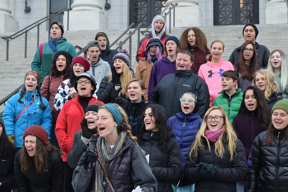 Holly Lammert, front, a teacher from Realms of Inquiry, leads a chant in support of public lands outside the Capitol on Thursday - RAY HOWZE