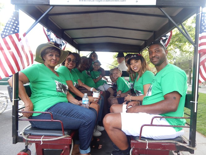 Green Flake's descendants get settled in their wagon before Wednesday's Days of '47 Parade. - PETER HOLSLIN