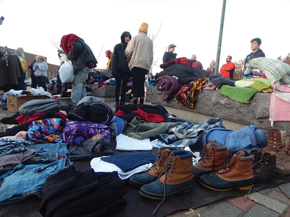 Acitivsts handed out winter clothes near The Road Home shelter last week while calling on officials to keep the shelter open until April. - PETER HOLSLIN