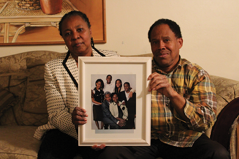 Marie Micheline and Joseph Ernst Montfleury hold up a family portrait taken during happier times inside their Orem home. At the time, their eldest son, Mackenley, was held in a Colorado detention facility, where he remained in immigration limbo. - ENRIQUE LIMÓN