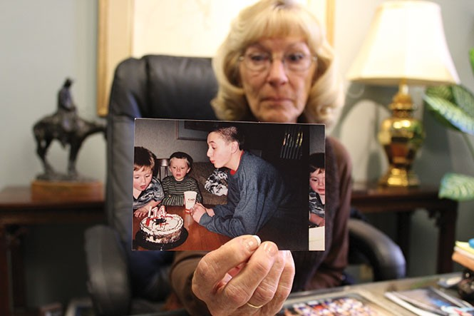 Brock Tucker's grandmother, Janet Crane, holds up a memento depicting happier times on Monday, Oct. 10. - ENRIQUE LIMÓN