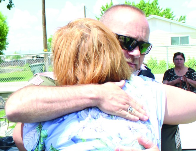 Detective David Brewer gives Heidi Jones-Asay a hug just before the body of her mother is reinterred at the Elmo Cemetery in Emery County.