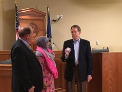 Jim McConkie, right, gives Noor Ul-Hasan a refugee rights card. - DW HARRIS