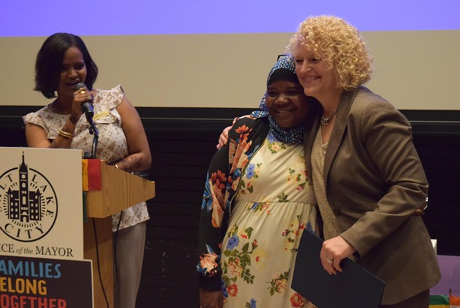 Aziza Hussein is embraced by Mayor Jackie Biskupski after receiving an award at the World Refugee Day celebration. - RAY HOWZE