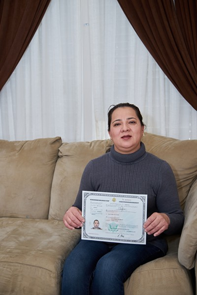 Elvia Perez Arizmendi holds up her Certificate of Citizenship inside her Sandy Home. - SARAH ARNOFF