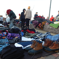 Acitivsts handed out winter clothes near The Road Home shelter last week while calling on officials to keep the shelter open until April.