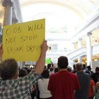 A Protester holds up an anti-HB155 sign last Friday at the Capitol.