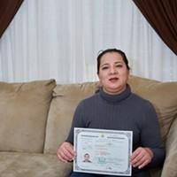 Elvia Perez Arizmendi holds up her Certificate of Citizenship inside her Sandy Home.
