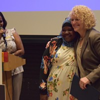 Aziza Hussein is embraced by Mayor Jackie Biskupski after receiving an award at the World Refugee Day celebration.
