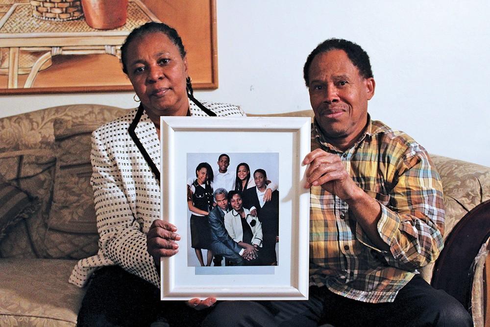 Marie Micheline and Jospeh Ernst Montfleury hold up a family portrait taken during happier times. - ENRIQUE LIMÓN