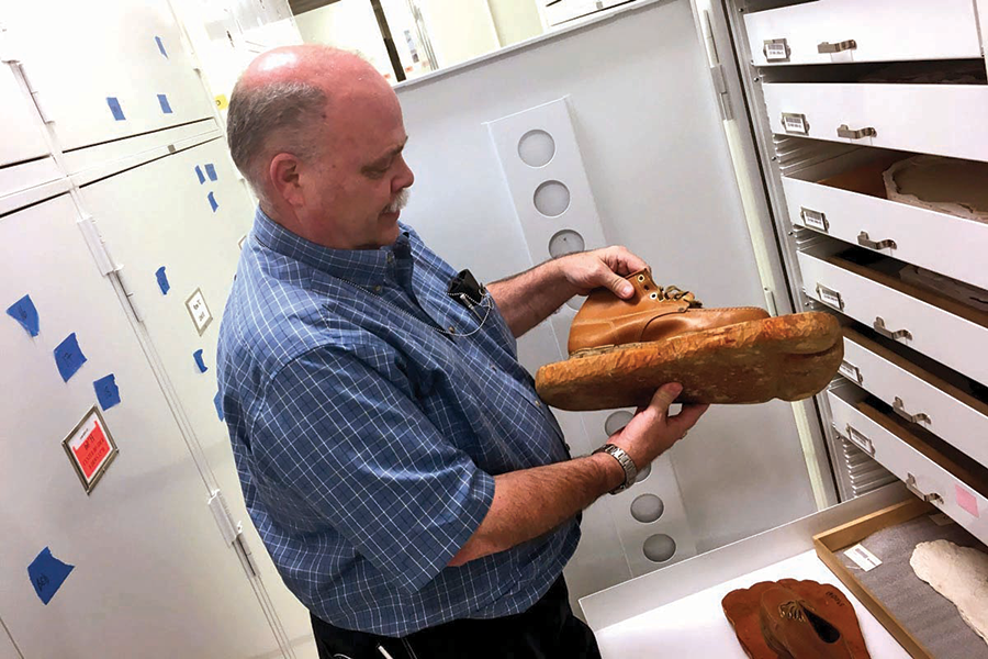 Dr. David Hunt holds up a carved wooden foot nailed to a boot belonging to anthropologist Grover Krantz. Krantz built these faux feet to demonstrate what fake Bigfoot footprints would look like. - LAURA KRANTZ