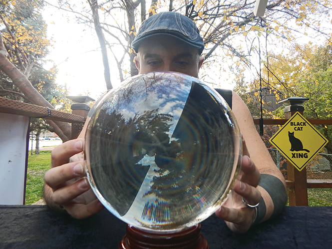 "Michael Ingleby, the ""friendly neighborhood witch"" of magic shop Cat & Cauldron, tells City Weekly's fortune on his trademark crystal ball. - PETER HOLSLIN"