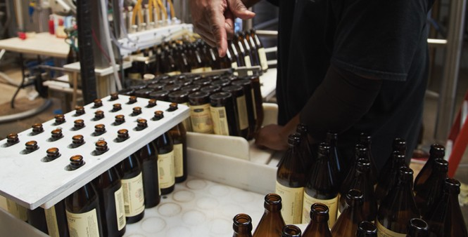 14. Giles moves newly labeled bottles to be filled and capped.