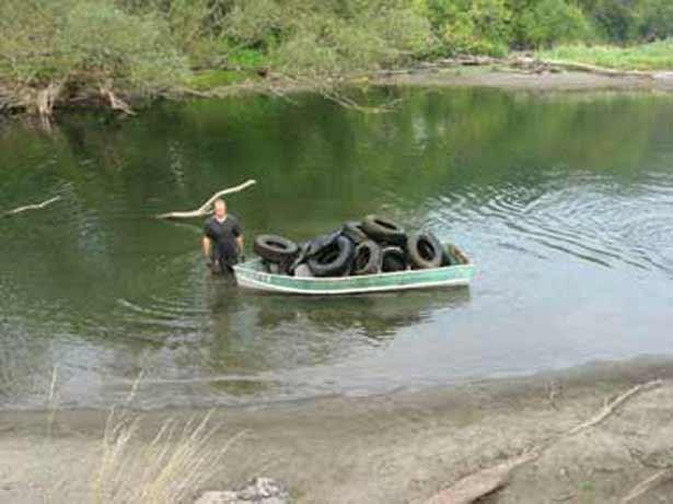 A volunteer cleans up scrap tires in the Winooski River last Saturday