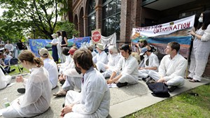 Activists outside the Public Service Department in Montpelier on Monday