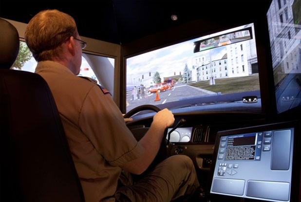 An officer behind the wheel of an L3-MPRI driving simulator.
