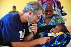 Pediatrician Barry Finette examines a child at a clinic in Togo. - FILE PHOTO COURTESY OF DR. BARRY FINETTE