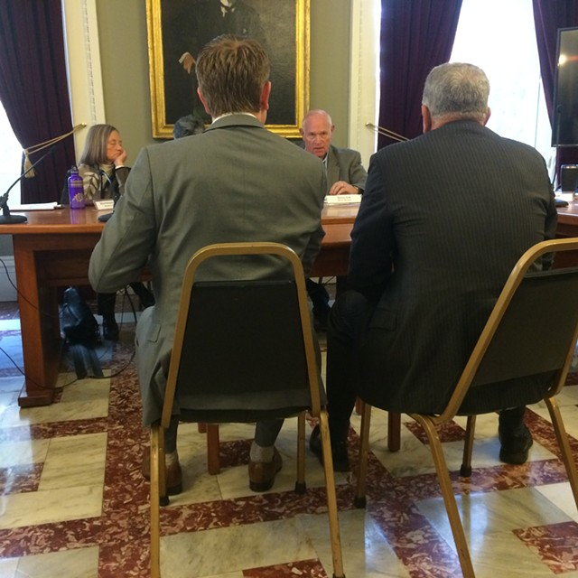 CCA officials from left, Daniel Kaman and Kevin Myers, talk to Sen. Dick Sears (D-Bennington) during a Joint Legislative Corrections Oversight Committee meeting. - MARK DAVIS