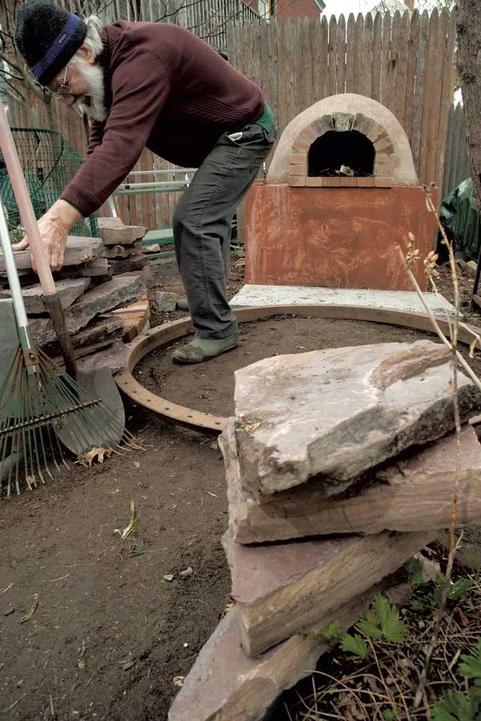 Charlie McClintock finishes the hardscaping around the pizza oven constructed last fall. - MATTHEW THORSEN