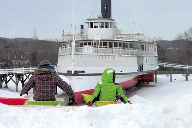Children sledding on the hill near the Ticonderoga - MATTHEW THORSEN