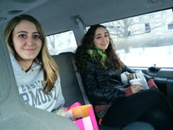 Christina Hart, left, and Zoe Gagnon, right, share a taxi ride from their jobs at the University Mall home to downtown Burlington Monday evening. - ALICIA FREESE