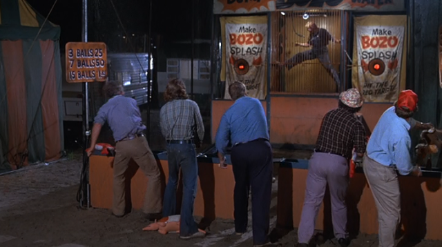 Drunken yahoos try to pelt Gary Busey in the dunk tank. - WARNER BROS. PICTURES