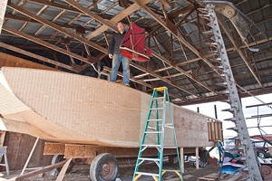 MATTHEW THORSEN - Erik Andrus stands atop his sail barge holding a model of what it will look like when finished