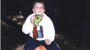 HEAVYWEIGHT CHAMP John Sholtz, age 7, and his prize-winning 347-pound pumpkin