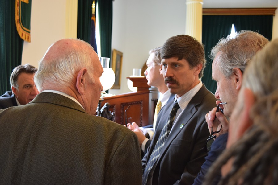 Sen. John Rodgers (D-Essex/Olreans), right, talks to Sen. Dick Sears (D-Bennington) about a measure to legalize the use of gun suppressors Friday on the Senate floor. - TERRI HALLENBECK