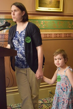Mia Hockett, a Burlington doctor and mother, talks Tuesday at the Statehouse about the need for vaccinations. Her 4-year-old daughter, Merin, has leukemia, which compromises her immune system. - TERRI HALLENBECK