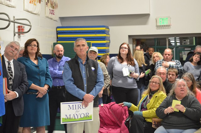 "Dave Hartnett holds a ""Miro for Mayor"" sign at the Democratic caucus. His opponent, Carmen George, is in the blue suit. - ALICIA FREESE"