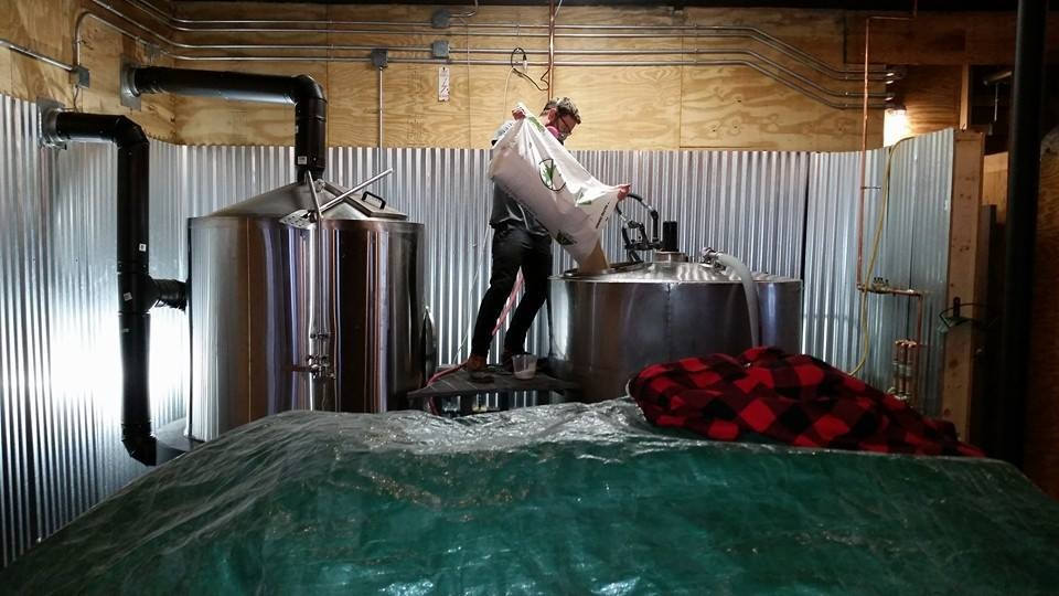 Nate Johnson mashing in the first brew in Prohibition Pig's new brewery last Friday. - COURTESY CHAD RICH/PROHIBITION PIG