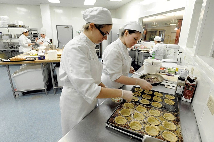 Rachel Kalinowski, left, and Lauren Layman fill savory mini quiches at NECI in Montpelier - JEB WALLACE-BRODEUR