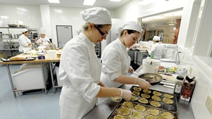 Rachel Kalinowski, left, and Lauren Layman fill savory mini quiches at NECI in Montpelier
