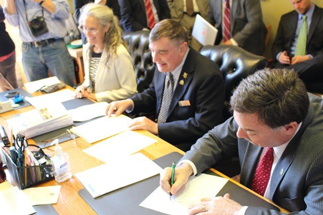 Rep. Patrick Brennan (R-Colchester) signs off on legislation banning the use of cellphones while driving. - PAUL HEINTZ