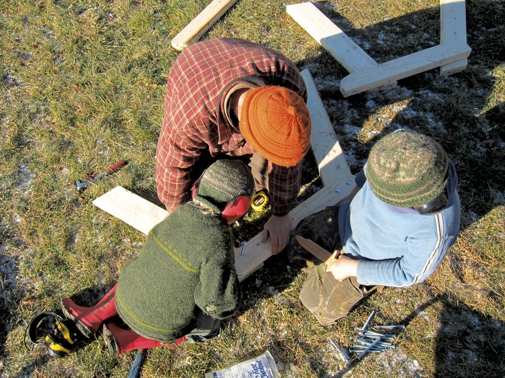 Rye, Ben and Fin Hewitt building a picnic table