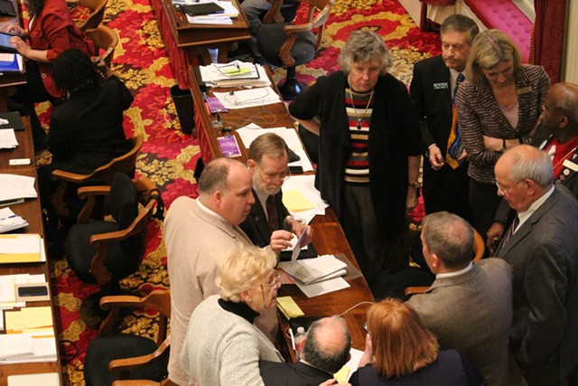 The House Education Committee huddles on the House floor Wednesday. - PAUL HEINTZ