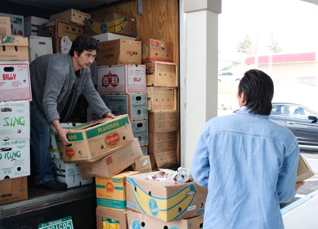 Thanh Pham (left) unloads produce from his truck