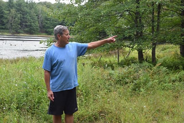 Former Lt. Gov. Brian Dubie points to the location of proposed wind turbines on land behind his house in Fairfield on the Swanton town line.