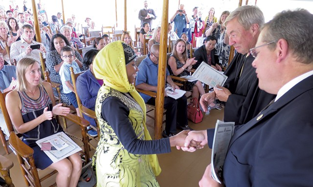 Judge Sessions congratulates a newly naturalized American aboard the Ticonderoga steamboat at Shelburne Museum this September. - MATTHEW THORSEN