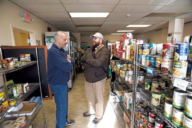 Rev. John Longworth (right) talking with Rodney Palmer at the BROC Community Action in Southwestern Vermont Food Shelf - CALEB KENNA