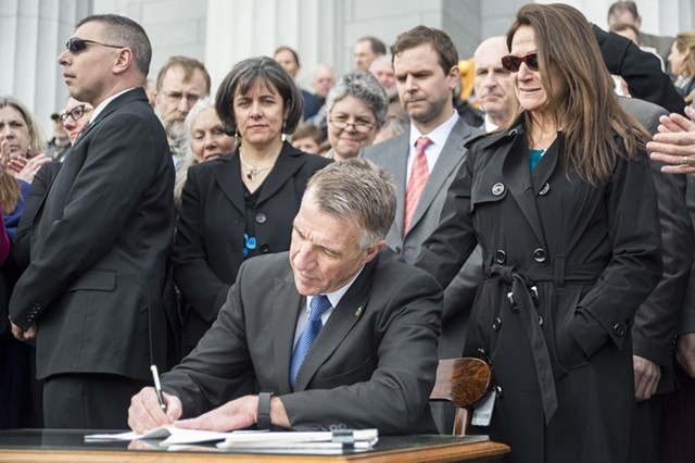 Gov. Phil Scott, joined by his wife Diana McTeague Scott, signs the bills into law amid a mixture of applause and jeers. - JOSH KUCKENS