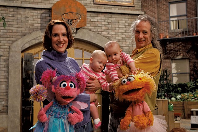 "Annie Evans and Martin P. Robinson with their twins and Muppets - COURTESY OF ""SESAME STREET"""